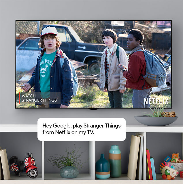 "TV de pantalla plana montado en la pared en una sala de estar moderna. Escena de Stranger Things de Netflix en la pantalla. Burbuja de comentario: ""OK Google, reproduce Stranger Things de Netflix en mi TV""."