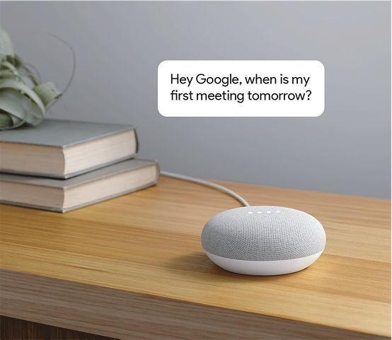 """Google Home Mini con la burbuja de comentario arriba que dice: """"Oye Google, ¿a qué hora es mi primera reunión mañana?"""""""